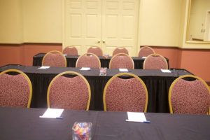 rows of tables and chairs in meeting room